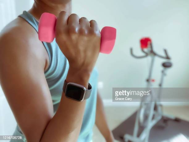 woman holds lightweight dumbbell - human muscle stock pictures, royalty-free photos & images