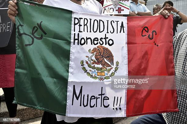 A woman holds Mexican flag with an inscription that reads 'To Be a Honest Journalist is Death' during a demonstration for the murder of...