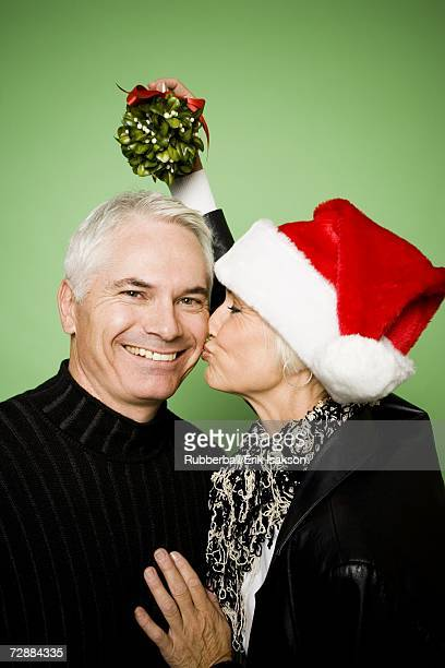 A woman holds mistletoe over a man's head while kissing him on the cheek