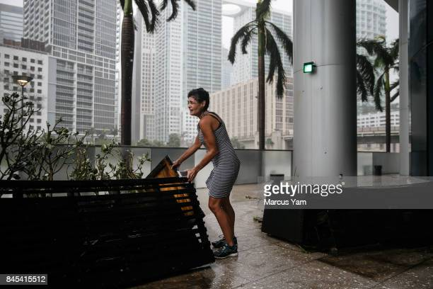 A woman holds on for her dear life as heavy winds caused by street as Hurricane Irma blows through the waterfront on the Miami River in Miami Fla on...