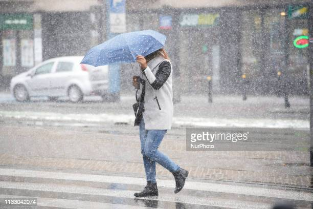 A woman holds on to her umbrella during a storm in Warsaw Poland on March 26 2019 A sudden hail storm strong winds and a drop in temperature occured...