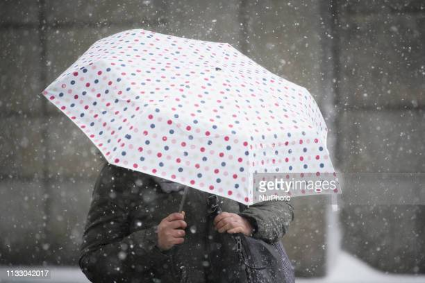 A woman holds on to her umbrella during hail storm in Warsaw Poland on March 26 2019 A sudden hail storm strong winds and a drop in temperature...