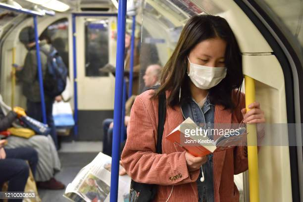 A woman holds on to the handrail as she reads a book while wearing a face mask on the Picadilly Line tube train on March 02 2020 in London England...