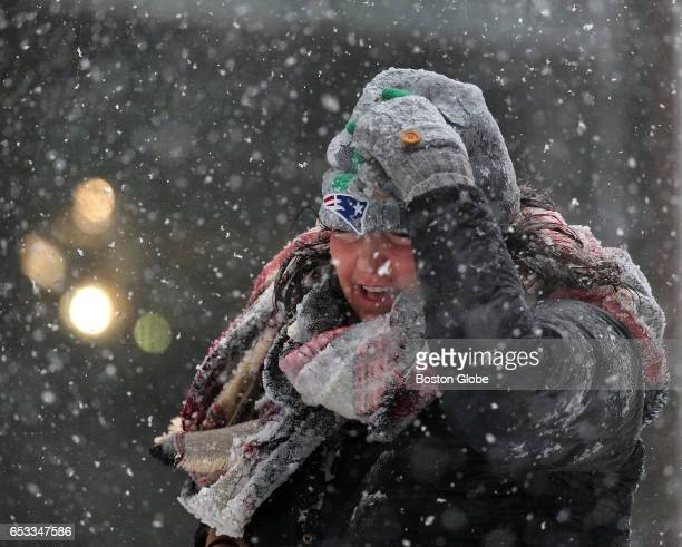 A woman holds onto her hat in the wind at Court Street in Boston during a winter storm on Mar 14 2017