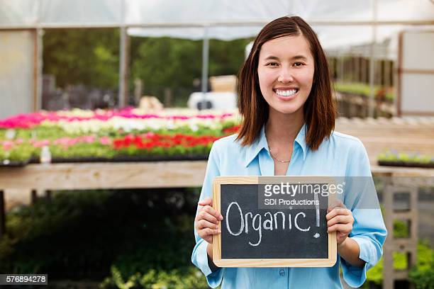 Woman holds 'Organic!' sign in garden center