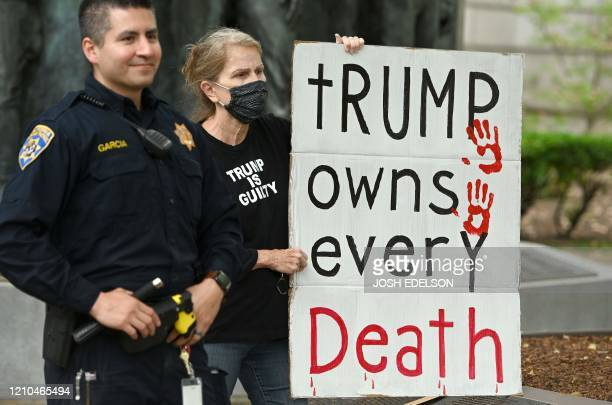 Woman holds out a sign blaming US President Donald Trump for Coronavirus deaths as hundreds of people gather to protest the lockdown in spite of...