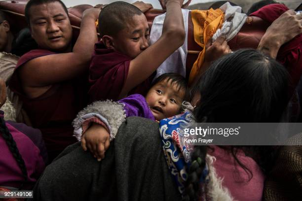 A woman holds out her child to be blessed by passing Tibetan Buddhist Monks of the Gelug or Yellow Hat school as they carry a rolled up giant thangka...