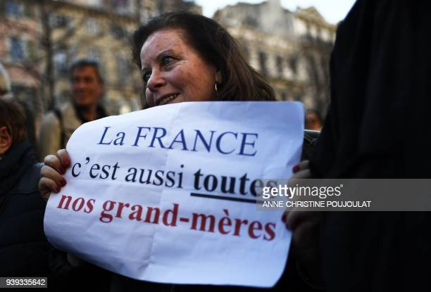 A woman holds placard reading 'France is also all our grand mothers' during a gathering in Marseille on March 28 in memory of Mireille Knoll an...