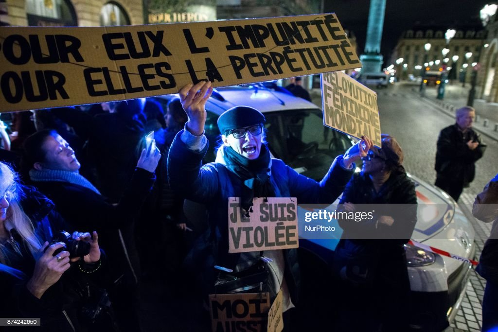 A woman holds placards reading « For them impunity for hers perpetuity » (R), « I am raped » (C) and « World feminine revolution » (L) as she takes part in a demonstration in front of the French Justice Ministry, in Paris, on November 14, 2017 called by different feminists associations to protest against the acquittal for rape of a man who had sex with an 11 year old. Two court decisions involving 11-year-old girls have recently highlighted the shortcomings of French law that the government intends to tackle in 2018.