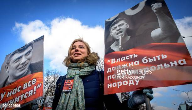A woman holds posters during an opposition march in memory of murdered Kremlin critic Boris Nemtsov in central Moscow on February 25 2018 The...