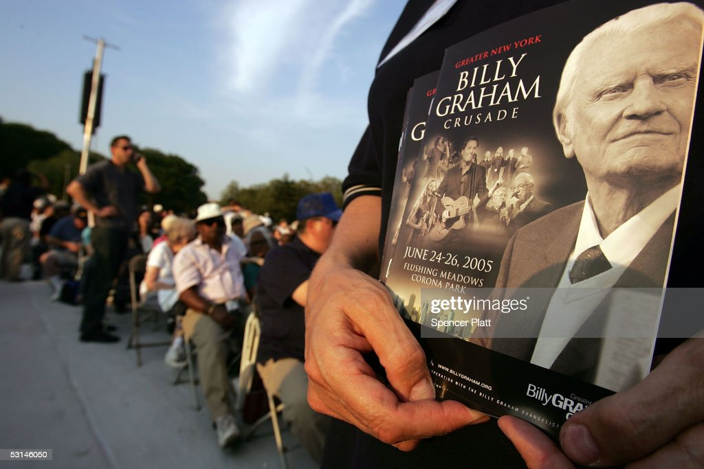 A woman holds programs at Flushing Meadows Corona Park before the start of the Billy Graham Crusade June 24, 2005 in the Queens borough of New York. Flushing Meadows Corona Park is the site for Graham's sermons on June 24-26. The Crusade, which looks to draw thousands of people from across the country, will purportedly be the aging Christian televangelist's final crusade.