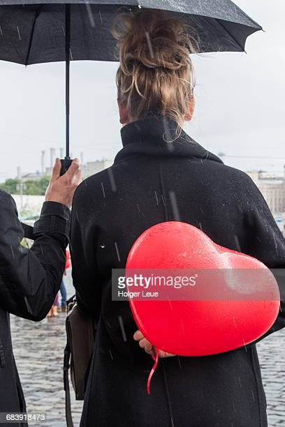 Woman holds red heart-shaped balloon behind back