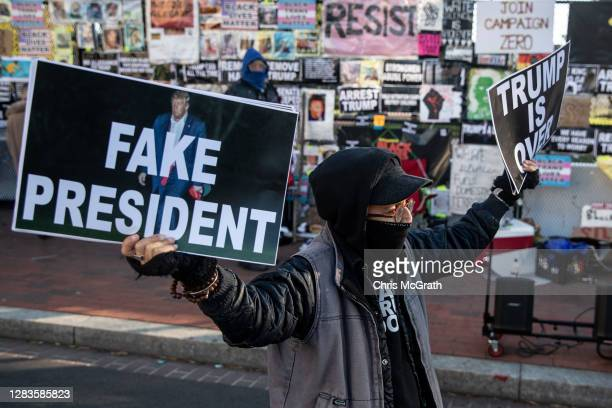 Woman holds signs protesting the president at Black Lives Matter Plaza near the White House on November 2, 2020 in Washington DC. Preparations...
