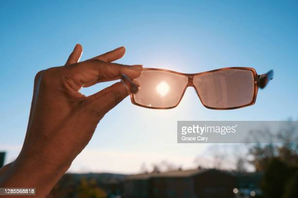 woman holds sunglasses against sky - uv protection stock pictures, royalty-free photos & images