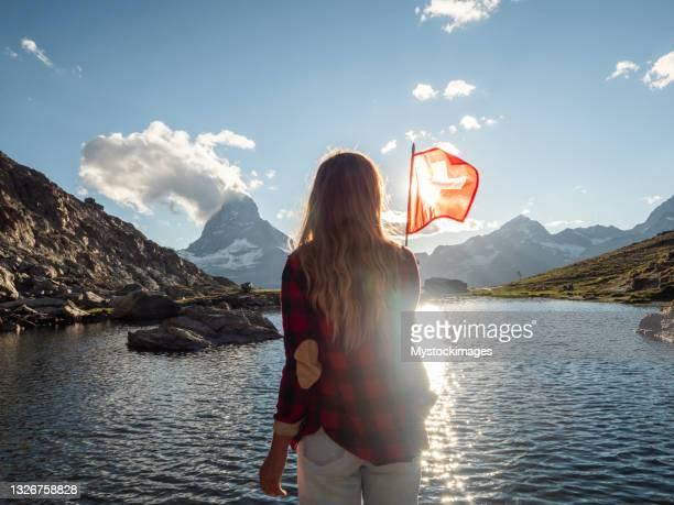 女性は山の風景に対してスイスの旗を保持しています, ツェルマット - 公的祝日 ストックフォトと画像