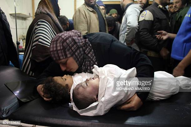 TOPSHOT A woman holds the bodies of two children as they lay on a surgical table at a makeshift hospital following reported shelling by government...