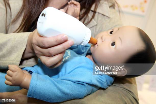 A woman holds the childcare simulation robot 'My Baby 2' by Realityworks during the 2007 International Robot Exhibition at Tokyo Big Site on November...