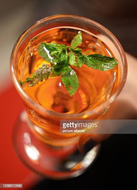 A woman holds the drink Aperol Spritz decorated with mint leaves and a mint flower in Berlin Germany 21 August 2013 Photo JENS KALAENE | usage...
