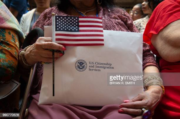 Woman holds the flag and her paperwork as the US Citizenship and Immigration Services welcomes 200 new citizens from 50 countries during a ceremony...