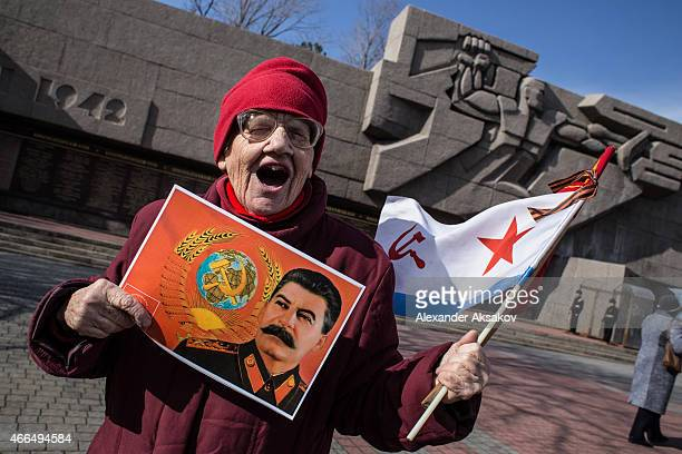 A woman holds the Flag of the Soviet Navy and a portrait of Stalin near the memorial of the heroic defense of Sevastopol as Crimeans celebrate the...