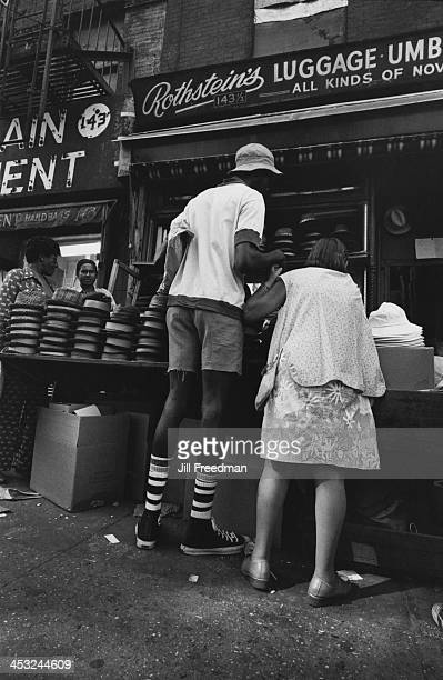 A woman holds the hand of a tall man as he browses the hats on sale at a market stall Lower East Side New York City 1975