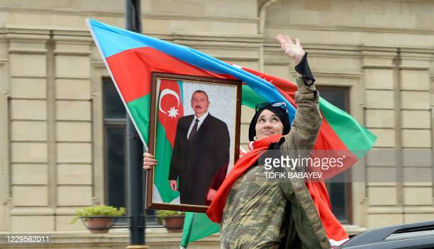 Woman holds the national flag and a portrait of Azerbaijan's President Ilham Aliyev as people celebrate in the streets of the capital Baku on...