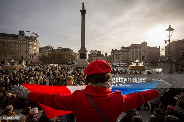 A woman holds the national flag of France as people gather in Trafalgar Square to show their respect to victims of the terrorist attacks in Paris on...