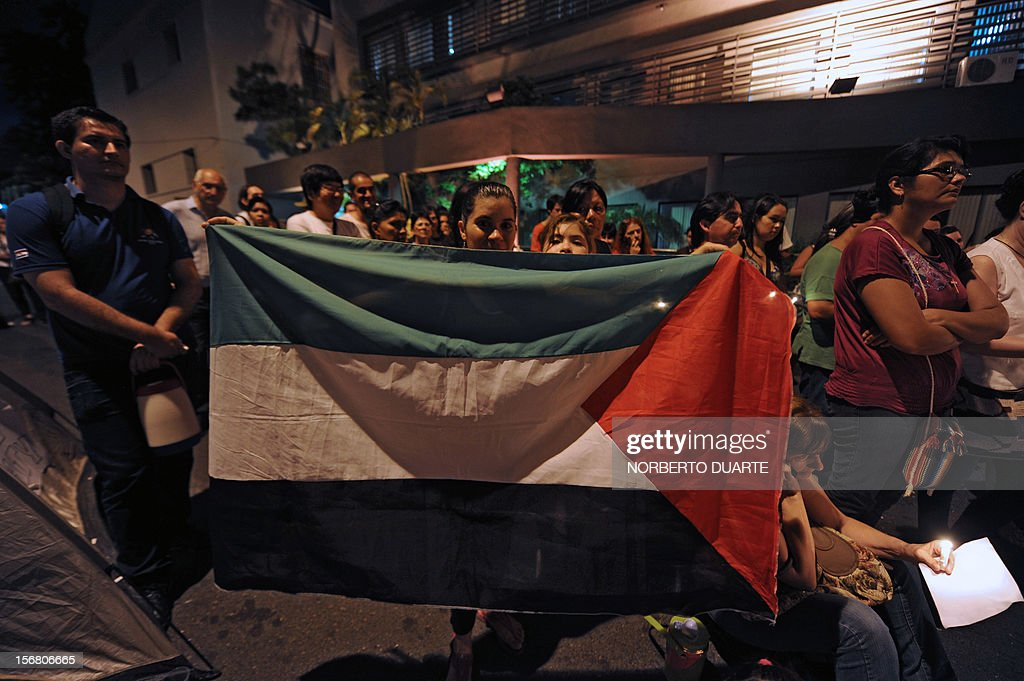 A woman holds the Palestinian flag during a vigil of supporters of ousted Paraguayan President Fernando Lugo and relatives of jailed peasants, in demand of their freedom, on November 21, 2012 in Asuncion. Four peasants accused -alongside other eight people- of the death of six policemen past June 15 in Curuguaty, 250 km northeast of Asuncion, remain on hunger strike. 11 peasants died in the confrontation with the police during the eviction of a private property. AFP PHOTO/ Norberto Duarte