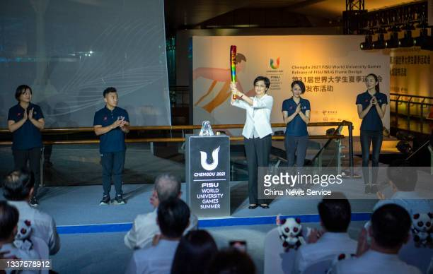 Woman holds the prototype design of the Chengdu 2021 FISU World University Games torch during its unveiling ceremony on August 31, 2021 in Chengdu,...