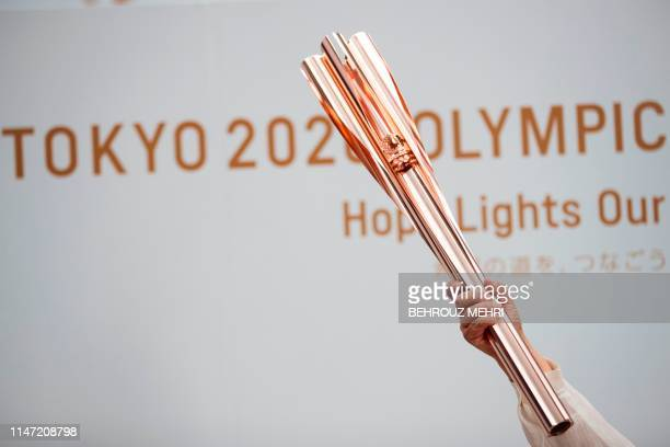 A woman holds the Tokyo 2020 Olympic Games torch during a public event in Tokyo on June 1 2019 The 2020 Tokyo Olympic torch relay will commence on...