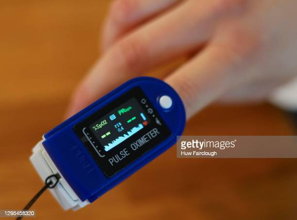 Woman holds their finger in a pulse oximeter as it takes a reading for their pulse and oxygen levels after they returned a Positive covid test, as...