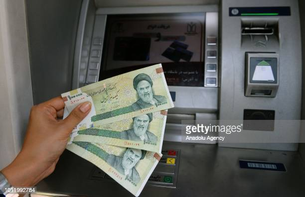 A woman holds toman near an ATM as toman devaluated to its lowest value against the US dollar last week besides the US will enforce sanctions against...