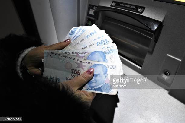 A woman holds Turkish lira banknotes in front of an ATM machine in Ankara Turkey on December 27 2018 A year is passed under economic difficulties as...