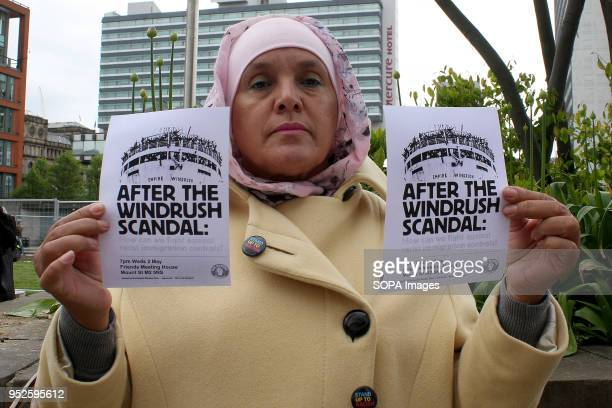 A woman holds two 'After the Windrush Scandal' flyers during an AntiRacism and 'WindrushGeneration' Protest on Manchester The protestors demanded and...