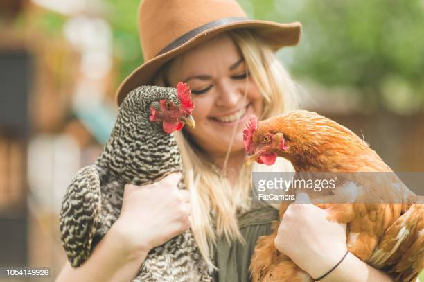 Woman holds two chickens in her back yard farm