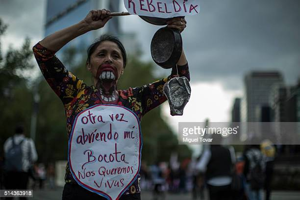 A woman holds up a banner during a protest commemorating the International Women's Day at Reforma Av on March 08 2016 in Mexico City Mexico