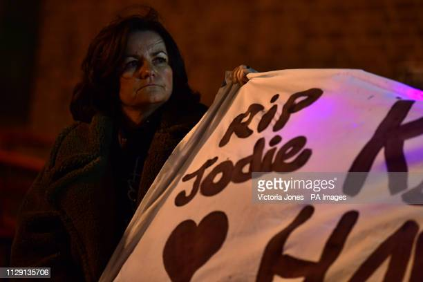A woman holds up a banner in Romford town centre as part of a protest of the fatal stabbing of Jodie Chesney who was playing music with friends near...
