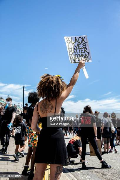 A woman holds up a Black Lives Matter placard during the protest in Brighton Local activists in England organised a protest in the centre of Brighton...
