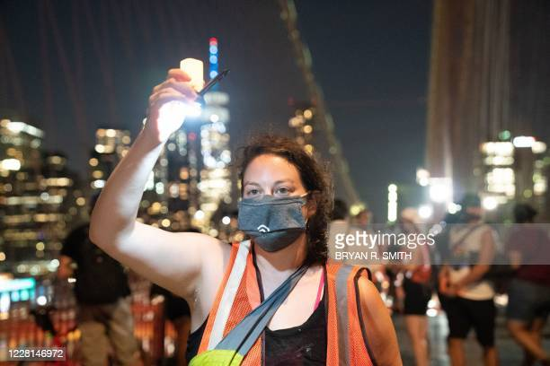 """Woman holds up a candle as people participate in the """"March for the Dead"""" across the Brooklyn Bridge, in memory of those who have died of COVID-19..."""