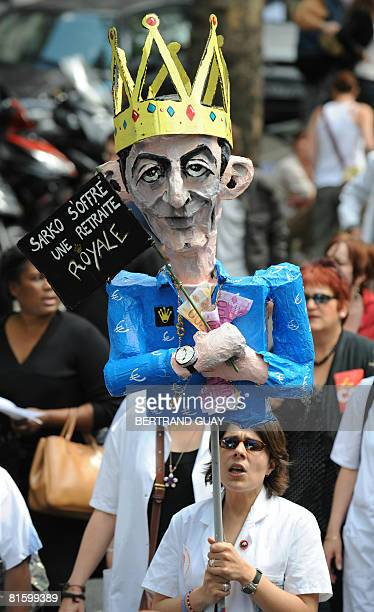 A woman holds up a caricature featuring French President Nicolas Sarkozy with a banner reading 'Sarko gives himself a royal pension' as she...