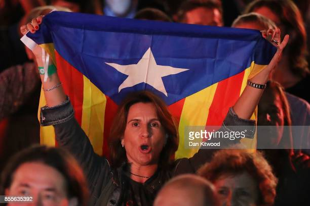 A woman holds up a Catalan flag as people gather at the final proindependence rally at Plaza Espana ahead of Sunday's referendum vote on September 29...