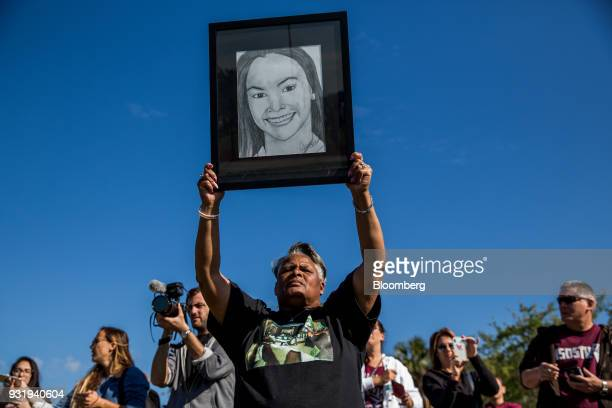 A woman holds up a drawing of Marjory Stoneman Douglas high school shooting victim Meadow Pollack during the ENOUGH National School Walkout rally in...