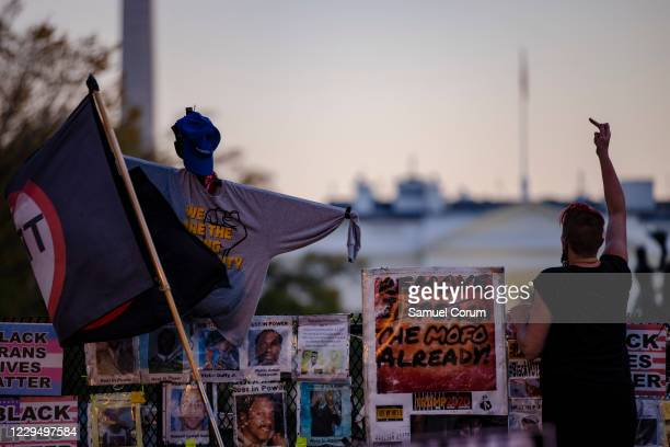 Woman holds up a finger as she climbs a temporary barrier during a demonstration at the Black Lives Matter Plaza in front of the White House on...