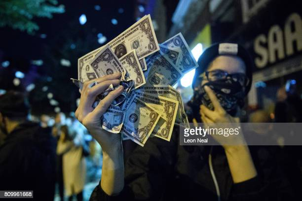 A woman holds up a handful of fake US currency during the ÒWelcome to HellÓ antiG20 protest march on July 7 2017 in Hamburg Germany Leaders of the...
