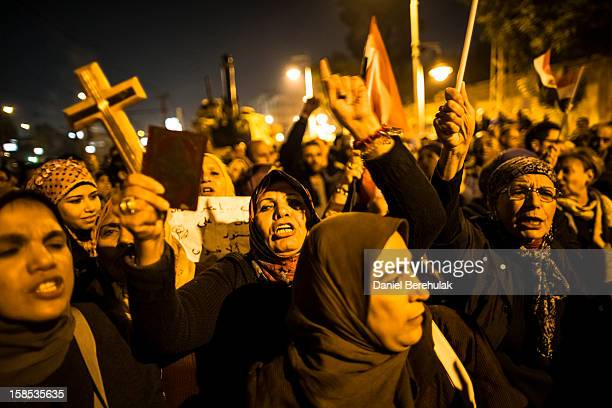 A woman holds up a Koran and a cross in her hand as Egyptian protestors opposing President Mohammed Morsi chant slogans during a demonstration at the...
