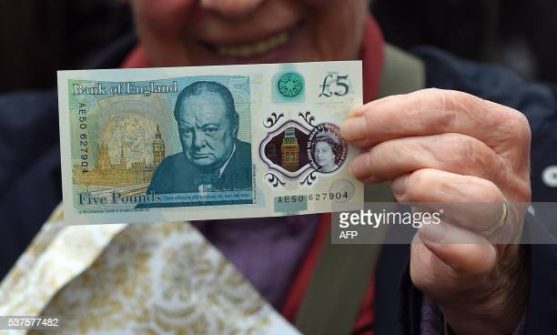 A woman holds up a new £5 banknote bearing the image of wartime leader Winston Churchill at its unveiling by the Bank of England at Blenheim Palace...