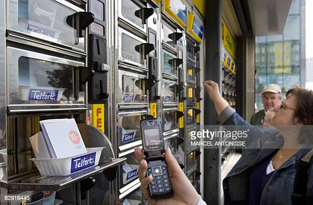 A woman holds up a new prepaid mobile phone near the Amsterdam Arena on September 19 2008 Dutch phone company Telfort and snack shop chain Febo have...