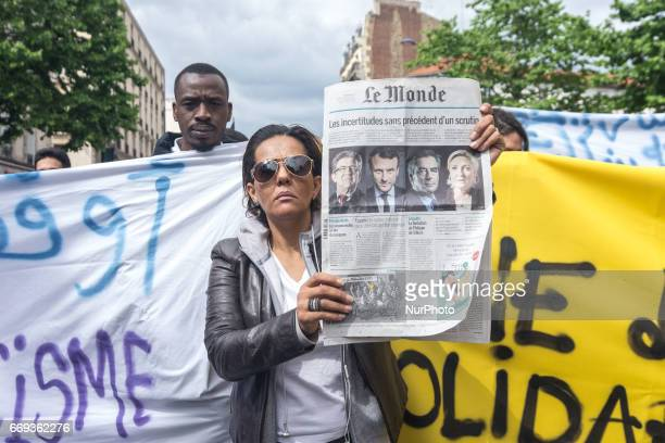 A woman holds up a newspaper as hundreds take to the streets for a march starting in suburban Aubervilliers in Paris France on April 16 2017 to...