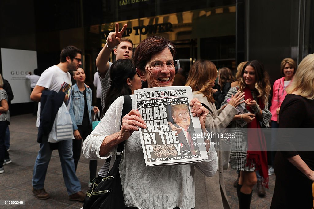 A woman holds up a newspaper with a headline quoting Donald Trump outside of Trump Tower in Manhattan October 8, 2016 in New York City. The Donald Trump campaign has faced numerous calls for him to step aside after a recording from 2005 revealed lewd comments Trump made about women.