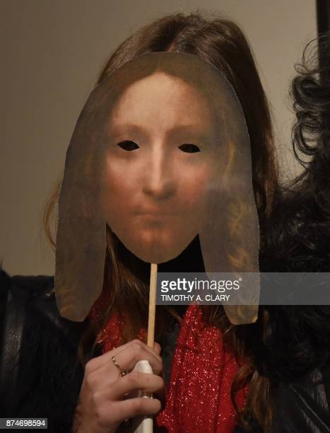 A woman holds up a paddle with the likeness of Leonardo da Vincis 'Salvator Mundi' as she arrives at Christie's before bidding takes place for the...